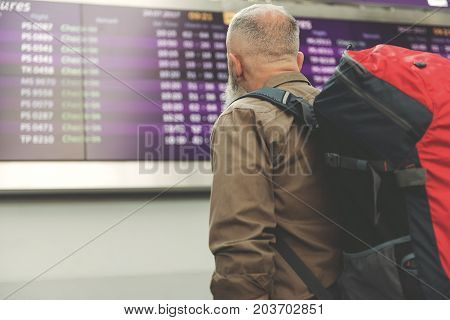 Bearded old man looking through timetable in airport hall. He turning back to camera. Copy space