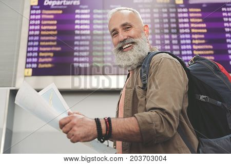 Low angle portrait outgoing unshaven old man looking at chart while standing in airport hall. He looking at camera