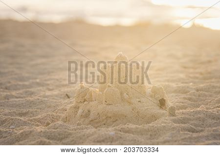 Holiday concept with sandcastle on the seaside.