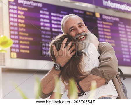 Portrait of happy bearded old man hugging little girl near timetable indoor airport