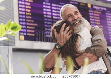 Portrait of unshaven beaming grandfather situating with child in airport hall. She turning back to camera