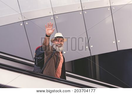 Portrait of outgoing unshaven old man flourishing arm while moving on travelling staircase