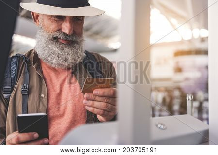 Portrait of outgoing bearded old man watching at credit card while keeping mobile in hand near terminal