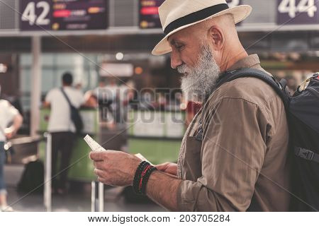 Side view serene unshaven grandfather looking at paper while standing in airport hall. Copy space
