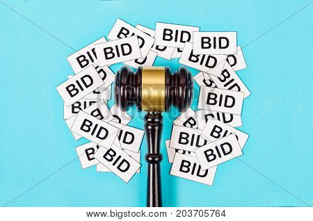 One gavel like those used on auctioning with the word bid on blue background.