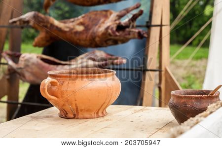 Ceramic Pot On A Wooden Table And Roasted Pig In A Background