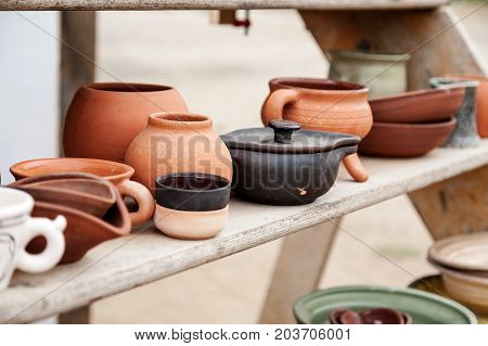Different Handmade Pottery On A Wooden Shelf, Selective Focus