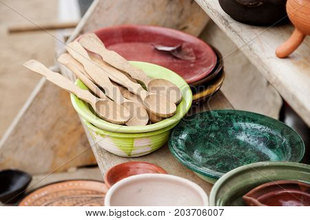 Different Color Pottery With Wooden Spoons On A Wooden Shelf