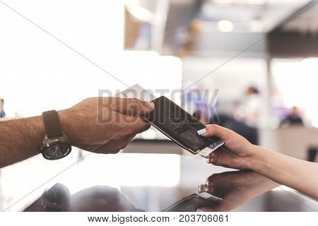 Focus on close up grandfather hand getting ticket on plane bound in booking office. Copy space
