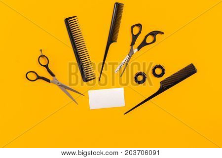 Hairdresser tools on yellow background with copy space, top view, flat lay. Comb, scissors, thinning scissors, hair clip. Still life.