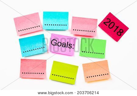 colorful sticky note paper with Goals 2018 on white wall background.
