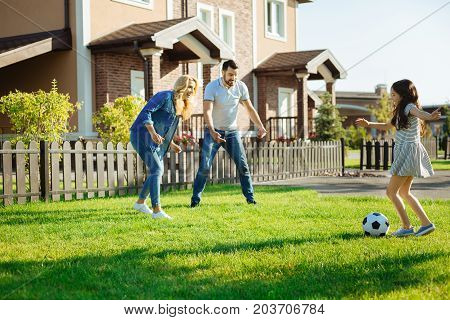 Family time. Adorable little girl playing football with her parents in the backyard, passing the ball to them