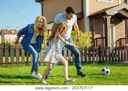 Energetic pastime. Upbeat happy family playing football on the green lawn in their backyard and running towards the ball altogether