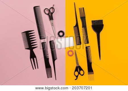 Hairdresser tools on pink and yellow background with copy space, top view, flat lay. Comb, scissors, thinning scissors, hair clip. Still life.