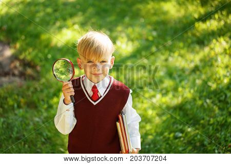 CCute boy going back to school. Child with books and loupe on first school day.