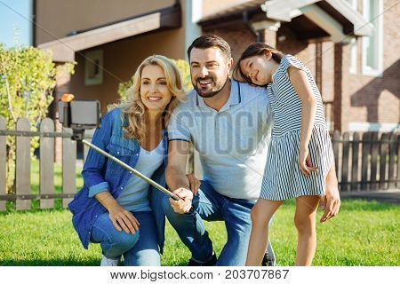 Collecting memories. Charming young man squatting on the lawn in between his wife and daughter and taking a selfie of his family with a selfie stick