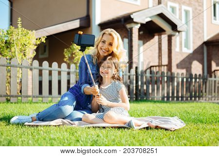 Precious moments. Adorable little girl sitting on the rug next to her pleasant mother and taking a selfie together with her, using a selfie stick