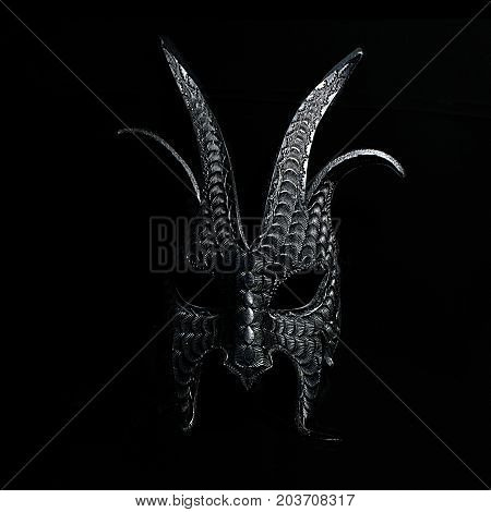 A scary Halloween mask in black and white against a black background. The mask is pointy and dark, with a macabre aspect. The mask face is in shadow, and would be a great trick or treat costume.