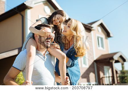 Treasured moments. Cute little girl sitting on the shoulders of her father, covering his eyes with her hands while her mother standing near them and laughing