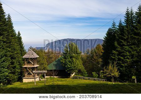 Viewpoint on a landscape of mount Bobija, meadow in front of an old wooden church surrounded by tall fir trees with rocky peaks in backgound, west Serbia