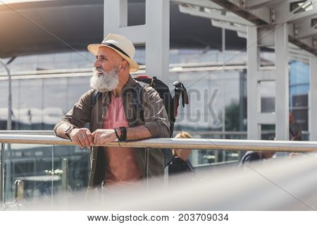 Joyous elder male tourist is putting hands on handrail and looking aside with happy smile. He wearing hat. Copy space on right side