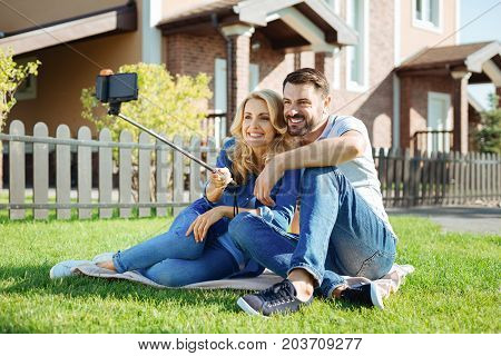 Forever in love. Cute middle-aged couple sitting on the rug in the backyard, cuddling and taking a selfie together with the help of a selfie stick