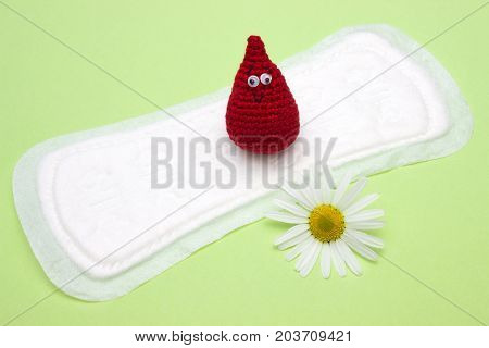 Feminine hygiene product medicinal chamomile flower blood drop on menstrual sanitary daily pad. Woman critical days menstruation cycle. Menstruation sanitary woman hygiene for blood period