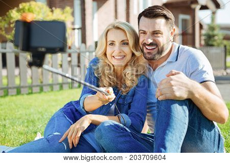 Family harmony. Cheerful young couple sitting on the ground in their yard and taking a selfie together with a selfie stick while smiling at the camera happily