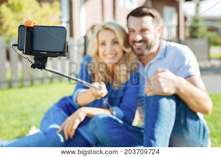 Sweet memories. The focus being on a selfie stick with a phone in it being held by a charming woman sitting next to her beloved husband and taking a selfie with him in their backyard