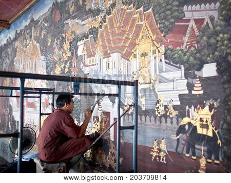 BANGKOK, THAILAND - JANUARY 28, 2011: Young restorer working in Wat Phra Kaew temple.