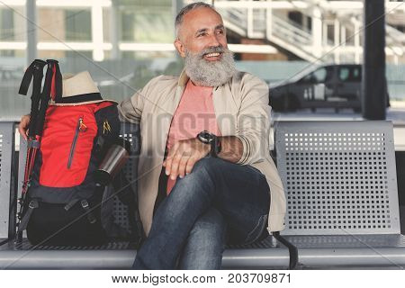 Joyous mature tourist is sitting at chair near his backpack in lounge. He looking aside with smile. Waist up portrait. Copy space on right side