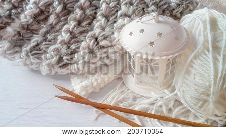 White yarn ball, knitted garment, wooden needles and white Christmas lantern on wood background