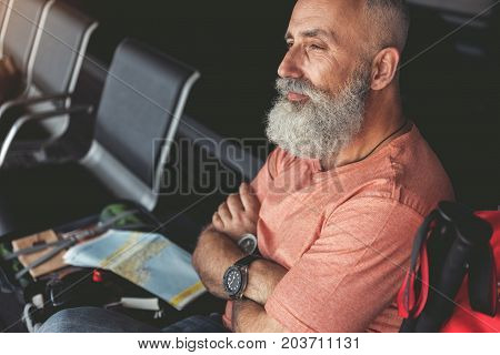 Thoughtful mature bearded tourist is sitting near open luggage and looking ahead with dreaminess. Profile. Copy space on left side