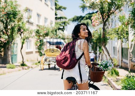 Young beautiful woman with dark hair rides a bike along the street. sunny day