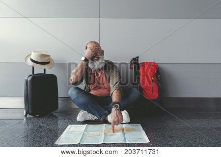 Cheerful mature tourist is sitting near wall. He closing eyes with one hand and choosing casual point on unfolded map. Portrait. Copy space on right side
