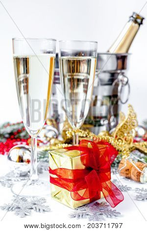 glasses of champagne and Christmas ornaments on white background.