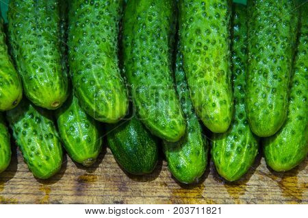Washed cucumbers are made up of two tiers on a wooden surface.