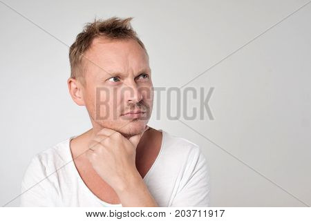 Portrait of handsome caucasian man looking with doubt up. Unsure in decision