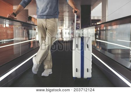 Man is standing on horizontal escalator and putting arm on case handle. Close up of male legs. Copy space on right side