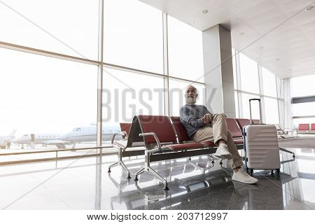Cheerful tourist is sitting on chair in hall of airport. He looking aside with light smile. Copy space on left side