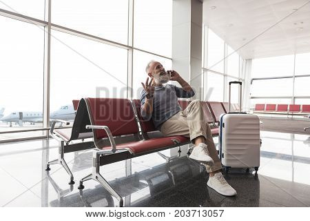 Joyous mature bearded man is sitting at chair near luggage and using phone for conversation. He looking ahead with laugh. Portrait. Copy space on left side