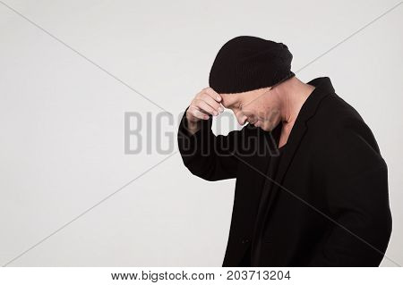 A young man in black clothes looks down in embarrassment. Side view. He thinks about something and smiles slightly.
