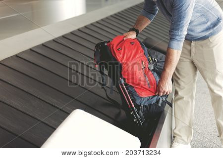 Man is standing near luggage tape and taking red backpack. Close up of bag in male hands. Copy space on left side