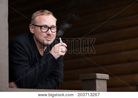 Caucasian man smoking new modern cigarette device. Hybrid technology between analog and electronic cigarettes. Heat not -burn tobacco product