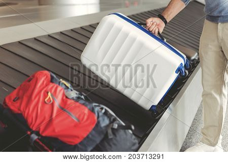 Man is taking his luggage. He standing near baggage tape in airport. Close up of bag in male hands. Copy space on left side
