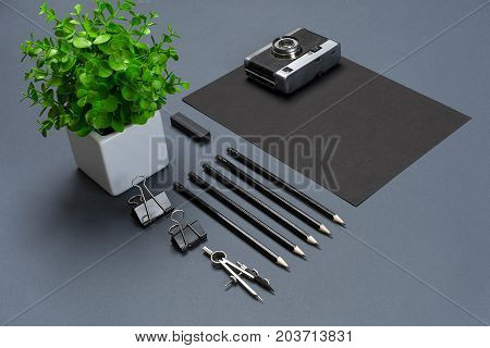 Modern mock up flat lay of blank black paper sheet and black stationery on gray background. Concept of creative work space