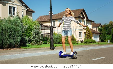 Sense of freedom. Inspired happy woman riding a hoverboard down the street and spreading hands, enjoying the freedom of a free ride