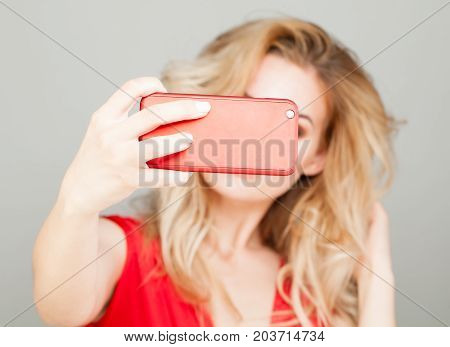 Selfie. Blonde Woman Taking Selfie with Smart Phone in Red Case