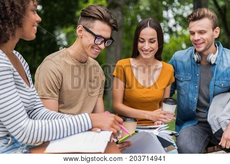 Joyful group mates are studying in campus outdoors together. They are sitting on bench and smiling