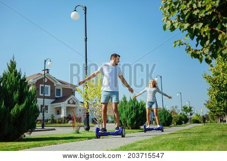 Enjoying fast ride. Upbeat lovely couple riding hoverboards one after another on the sidewalk down their street while spreading hands widely